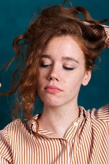 Donna graziosa del primo piano che tiene i suoi capelli in su
