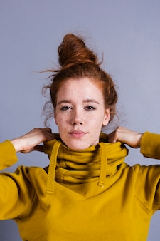 Donna graziosa del primo piano con il panino dei capelli e la maglia con cappuccio gialla