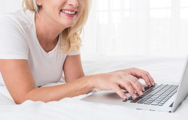 Donna graziosa del primo piano con sorridere del computer portatile