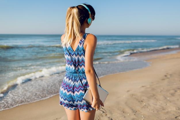 Donna graziosa del viaggiatore che ascolta la musica sulla spiaggia