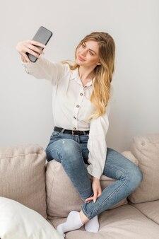 Donna graziosa della foto a figura intera che prende selfie