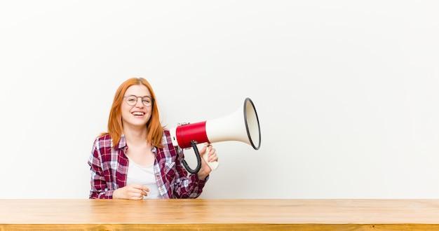 Donna graziosa della giovane testa rossa davanti ad una tavola di legno con un megafono
