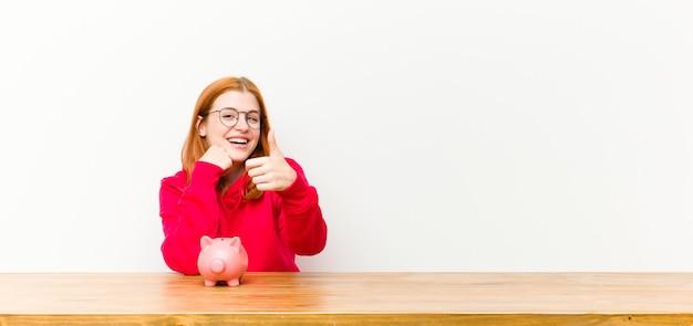 Donna graziosa della giovane testa rossa davanti ad una tavola di legno con un porcellino salvadanaio
