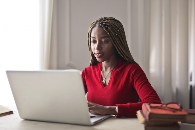 Donna graziosa di afro che lavora ad un computer portatile