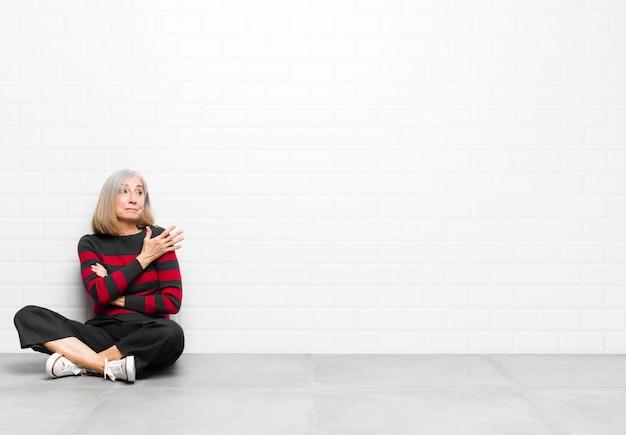 Donna graziosa di mezza età o anziana che si sente confusa e incapace, chiedendosi una spiegazione o un pensiero dubbioso