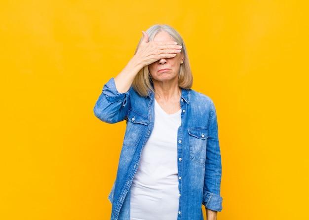 Donna graziosa di mezza età o senior che copre gli occhi con una mano sentendosi spaventata o ansiosa, chiedendosi o aspettando ciecamente una sorpresa