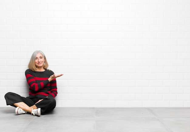 Donna graziosa di mezza età o senior che sorride allegramente, sentendosi felice e mostrando un concetto nello spazio della copia con il palmo della mano