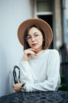 Donna graziosa di moda di strada con manicure rosso e occhiali trasparenti, seduto al tavolo