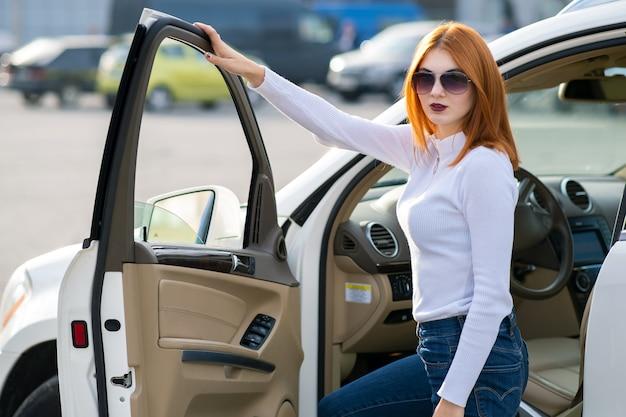 Donna graziosa di yong che sta vicino ad una grande automobile per qualsiasi terreno all'aperto. ragazza autista in abiti casual fuori dal suo veicolo.