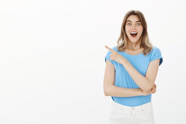 Donna graziosa emozionante che indica il dito lasciato a notizie sorprendenti, mostrando pubblicità