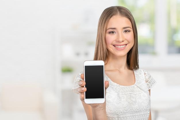 Donna graziosa felice che mostra uno schermo in bianco dello smart phone
