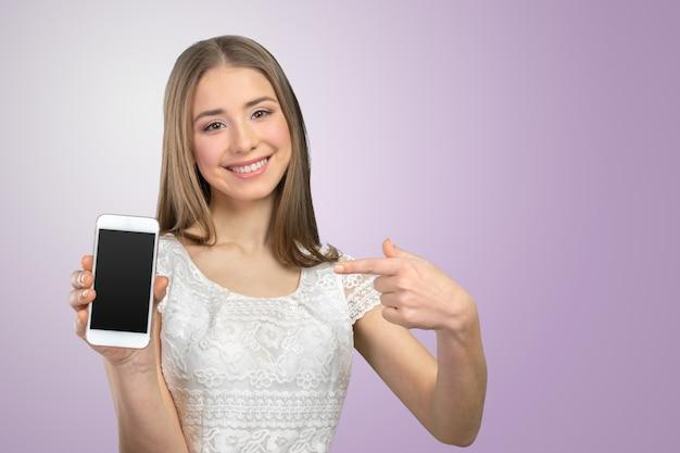 Donna graziosa felice che mostra uno smartphone in bianco