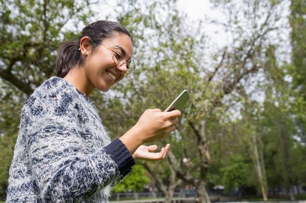 Donna graziosa felice che utilizza smartphone nel parco