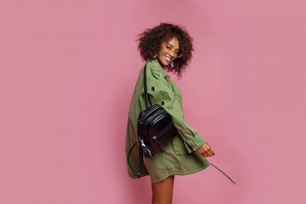 Donna graziosa formosa con pelle marrone che imbroglia e che posa nello studio su fondo rosa. peli afro.