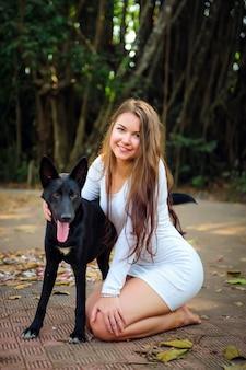 Donna graziosa in abito corto e cane nero che gioca all'aperto