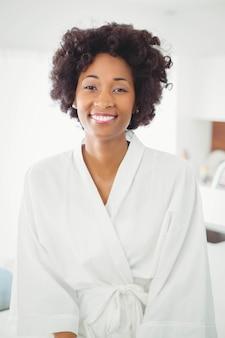 Donna graziosa in accappatoio che sorride alla macchina fotografica nella cucina a casa