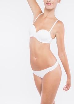 Donna graziosa in biancheria intima bianca che si leva in piedi sulla priorità bassa bianca