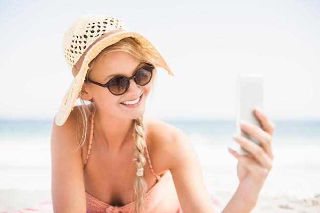 Donna graziosa in bikini e occhiali da sole che prendono un selfie sulla spiaggia