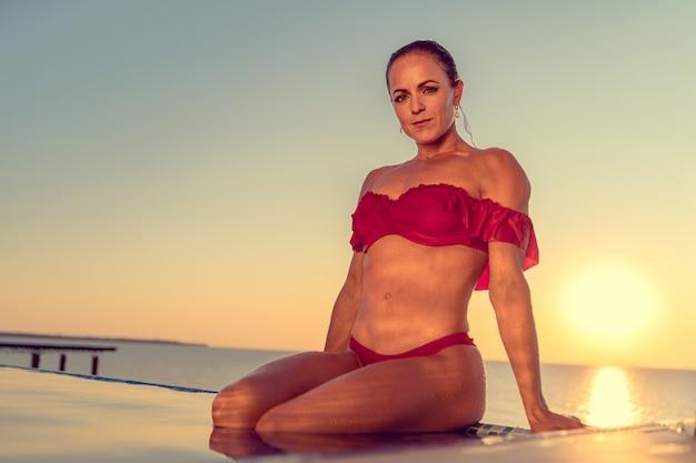 Donna graziosa in bikini rosso in un'acqua dello stagno