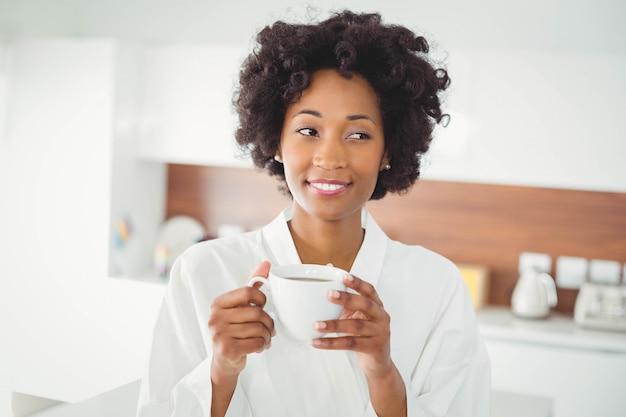 Donna graziosa in caffè bevente dell'accappatoio nella cucina a casa