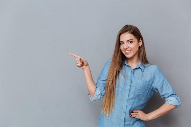 Donna graziosa in camicia che posa nello studio