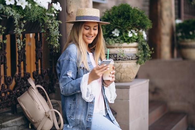 Donna graziosa in cappello che comunica sul telefono e che beve caffè