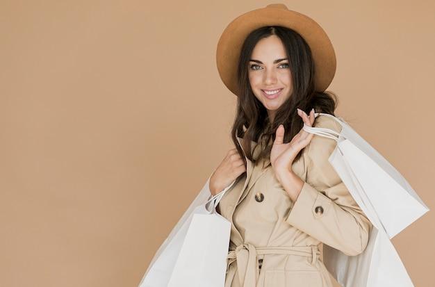 Donna graziosa in cappotto che esamina la macchina fotografica