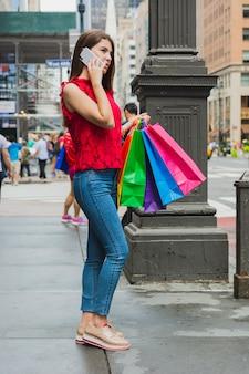 Donna graziosa in jeans che telefona con i sacchetti della spesa