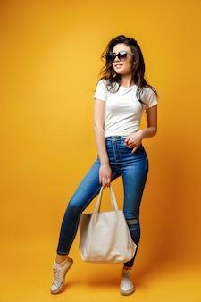 Donna graziosa in occhiali da sole con borsa