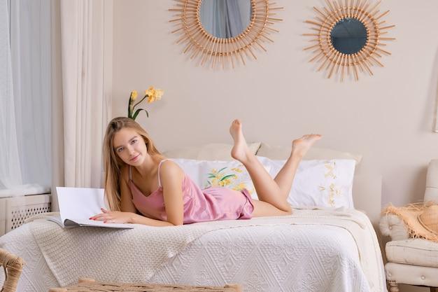 Donna graziosa in pigiama di seta a letto sfogliando una rivista