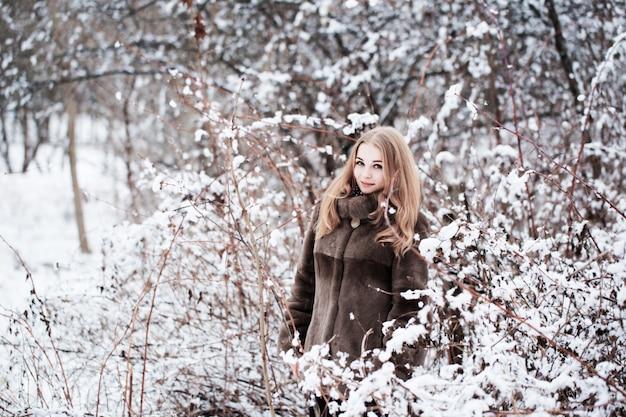 Donna graziosa in un parco di inverno
