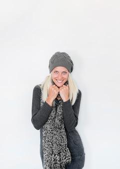 Donna graziosa in vestiti caldi che sorridono allegramente