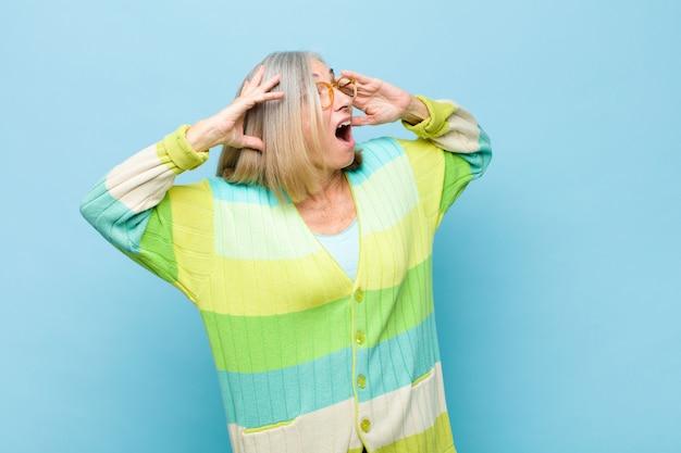Donna graziosa senior o di mezza età con la bocca aperta, che sembra inorridita e scioccata a causa di un terribile errore, alzando le mani alla testa