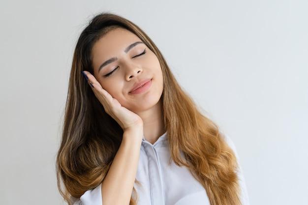 Donna graziosa serena che fa gesto di sonno con lei occhi chiusi