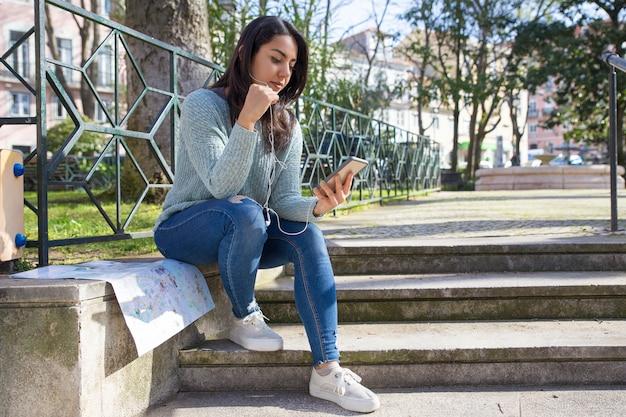 Donna graziosa seria che ascolta la musica sul parapetto delle scale della città