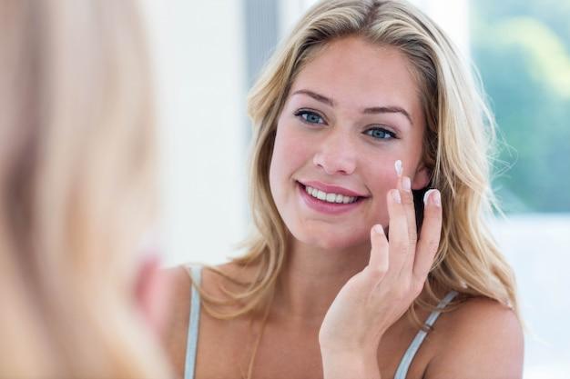Donna graziosa sorridente che applica crema sul suo fronte in bagno