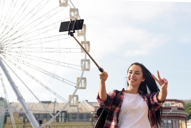 Donna graziosa sorridente che prende selfie con la mostra del gesto di vittoria che sta la ruota di ferris vicina