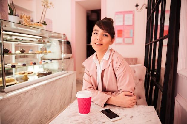 Donna graziosa sorridente che si siede al self-service e che beve caffè