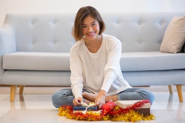 Donna graziosa sorridente che si siede sul pavimento con i regali di natale