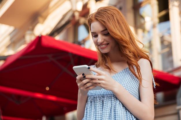 Donna graziosa sorridente della testarossa che per mezzo del telefono cellulare