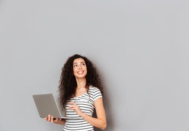 Donna graziosa sorridente in maglietta a strisce con il pensiero ascendente del fronte o sognare ad occhi aperti mentre lavorando tramite computer portatile che è isolato sopra la parete grigia