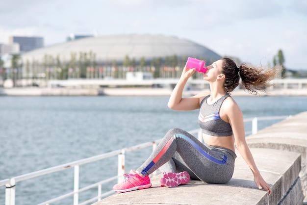 Donna graziosa sportiva bere da city river