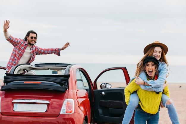 Donna gridante che tiene indietro signora felice vicino all'uomo che si appoggia fuori dall'automobile