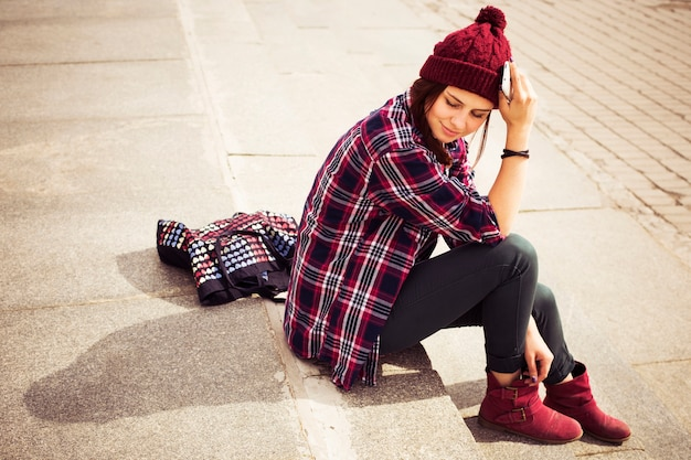 Donna hipster in abito casual seduto sui gradini in città con un telefono in mano