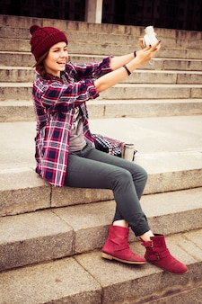 Donna hipster in abito casual seduto sui gradini in città, facendo selfie sulla fotocamera istantanea