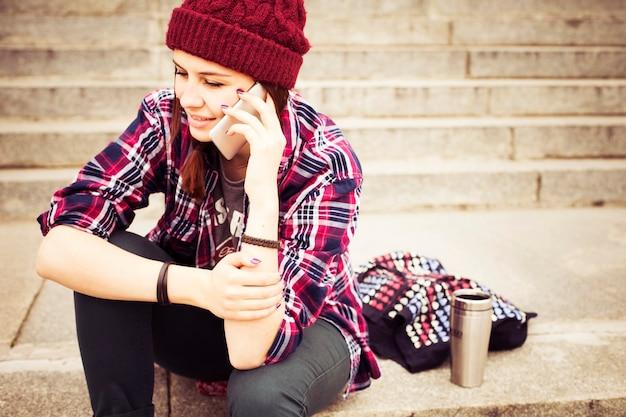 Donna hipster in abito casual seduto sui gradini in città, facendo telefonata
