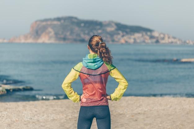 Donna in abbigliamento fitness in piedi e guardando la spiaggia di sein durante il giorno