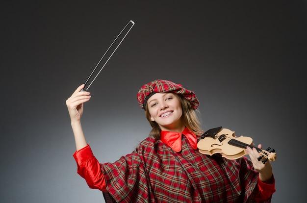 Donna in abbigliamento scozzese nel concetto musicale