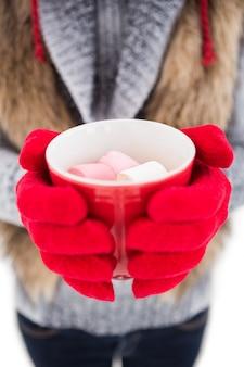 Donna in abiti invernali in possesso di una tazza