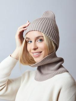 Donna in abiti primaverili, sciarpa snood, cappello e guanti. donna bionda con gli occhi azzurri.
